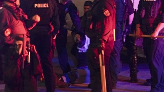 Louisville police detain a protester