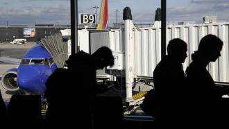 Travelers wait in line to board a flight.