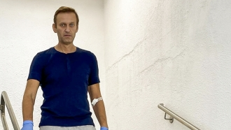 Russian opposition leader Alexei Navalny walks down stairs in a hospital in Berlin, Germany.