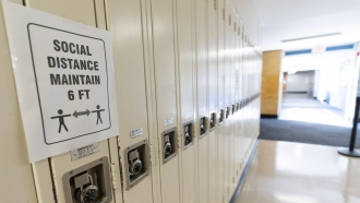 """Sign reads """"Social Distance Maintain 6 ft"""" on student lockers at a school"""
