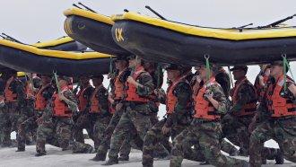 Navy SEAL trainees carry inflatable boats at the Naval Amphibious Base Coronado in Coronado, Calif.