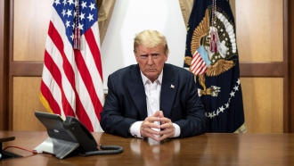 President Donald Trump listens during a phone call in his conference room at Walter Reed National Military Medical Center.