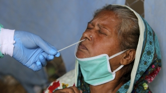 A health worker takes a nasal swab sample of a woman at a testing facility for the coronavirus in a hospital in Pakistan.