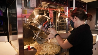 A Regal Cinemas employee makes popcorn at a theater in Irvine, Calif.