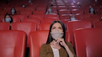Woman wearing face mask watches a movie at a cinema.