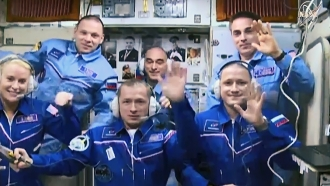 Expedition 64 crew members inside the space station's Zvezda service module.