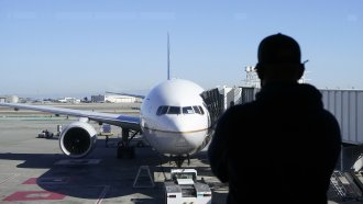 A man looks out of a window toward a United Airlines flight.