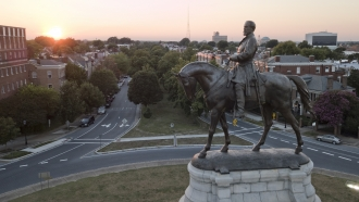 The sun sets behind the statue of Confederate Gen. Robert E. Lee on Monument Avenue in Richmond.