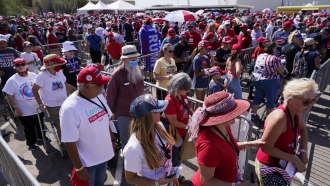 Supporters of President Donald Trump wait in line to attend a campaign rally Monday, Oct. 19, 2020, in Tucson, Arizona.