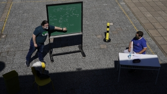A teacher leads a lesson outdoors at the school Hipólito Yrigoyen in Buenos Aires, Argentina.