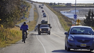 A biker leads a line of cars driving on Monday, Oct. 19, 2020, in Homer, Alaska after a tsunami evacuation.