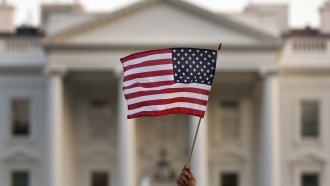 A flag is waved outside the White House.