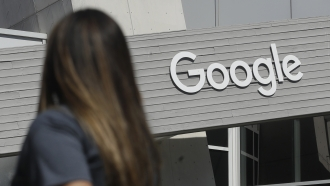 A woman walks by the Google sign on it's campus in Mountain View, California.