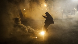 A demonstrator kicks a tear gas canister back at federal officers during a Black Lives Matter protest in Portland, OR July 20