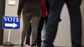 People wait in line to vote inside the DeKalb County elections office in Decatur on Monday morning October 12, 2020.