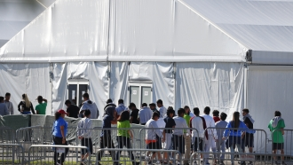 Children line up to enter a tent at the Homestead Temporary Shelter for Unaccompanied Children in Homestead, Fla. in 2019.