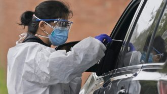 Medical personnel prepare to administer a COVID-19 swab at a drive-through testing site in Lawrence, N.Y.,