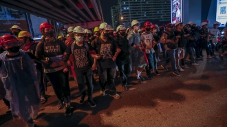 Pro-democracy activists create a human chain to confront a police barricades during their march in Thailand.