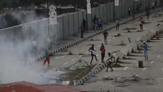 Protesters run away as police officers use teargas to disperse people demonstrating against police brutality in Nigeria.