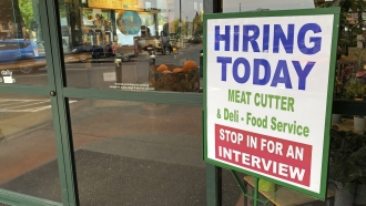 """A sign that reads """"hiring today"""" is shown at a grocery store."""