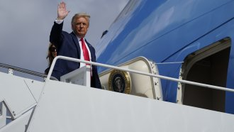 President Donald Trump waves as he and first lady Melania Trump board Air Force One to travel to Nashville, Tenn.,