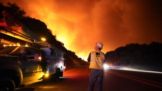 A Pacific Gas and Electric worker looks at the fire advancing along a northern California highway.