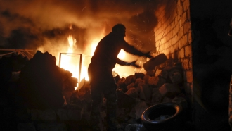 People try to remove car tires from a car shop on fire after shelling by Azerbaijan's artillery during a military conflict.
