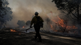 A firefighter prepares to put out hotspots while battling the Silverado Fire in California