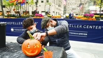 Sharif Butler and his nephew Chace, 11, carve pumpkins at Rockefeller Center