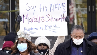 Marcellis Stinnette's mother holding a sign as she walks to a press conference.