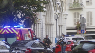 French policemen stand next to Notre Dame church after a knife attack, in Nice, France, Thursday, Oct. 29, 2020.