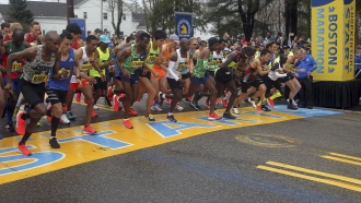 In this April 15, 2019, file photo, the elite men break from the start of the 123rd Boston Marathon in Hopkinton, Mass.