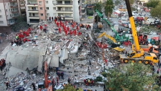 members of rescue services search for survivors in the debris of collapsed buildings in Izmir, Turkey.