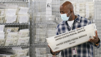 A worker collects absentee ballots for counting in New York.