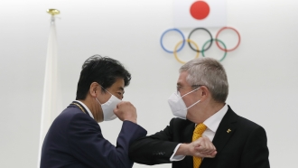 Former Japan's Prime Minister Shinzo Abe, left, and Thomas Bach, President of the International Olympic Committee.