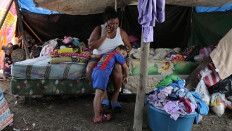 Wendy Guadalupe Contreras who was left homeless after the last storm hit the area, comforts her son in Honduras before Iota.