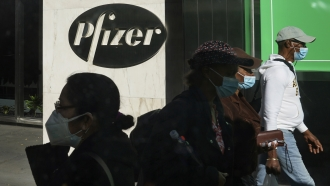 In this Nov. 9, 2020, file photo, pedestrians walk past Pfizer world headquarters in New York.