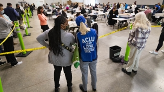 Democrat observers confer as they look on during a Cobb County hand recount of Presidential votes on Sunday, Nov. 15, 2020, i