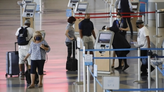 Travelers check in at the American Airlines terminal at the Los Angeles International Airport on May 28, 2020.