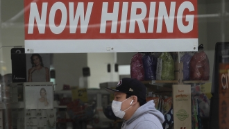 A man wearing a mask while walking under a Now Hiring sign at a CVS Pharmacy in San Francisco in May 2020.