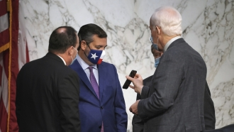 Sens. Mike Lee and Ted Cruz, R-Texas, look at the phone of Sen. John Cornyn