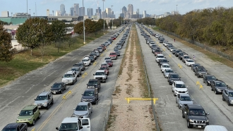 """Cars line up for """"Drive-Thru Mobile Pantry"""" as volunteers distributed 600,000 pound of food. Nov. 14 in Dallas' Fair Park."""