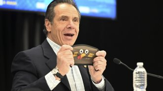 State of New York, New York Gov. Andrew Cuomo holds up a new Thanksgiving-themed face mask
