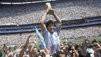 Diego Maradona holds up his team's trophy after Argentina's 3-2 victory over West Germany at the World Cup final.