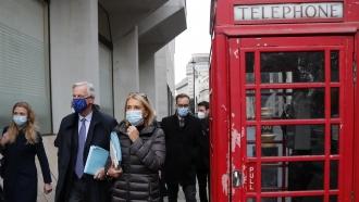 EU Negotiator Michel Barnier walks by an iconic UK phone booth