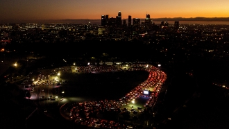 Motorists wait in long lines to take a coronavirus test in a parking lot at Dodger Stadium in Los Angeles, California