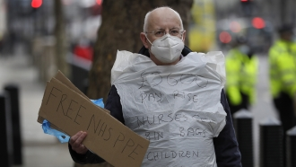A man campaigning for NHS PPE stands outside parliament in London