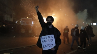 """A protester in Paris holds a poster reading """"Land of rights for the police"""" during a demonstration against a security law"""
