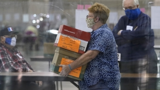An election official brings ballots during a Milwaukee hand recount of Presidential votes at the Wisconsin Center.