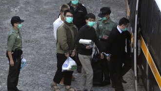 Hong Kong activists Joshua Wong, right, and Ivan Lam, left, are escorted by Correctional Services officers.